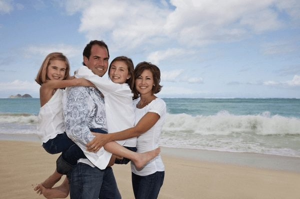 Beach Portrait of a family wearing white and denim clothes for a photo shoot at Waimanalo Beach, Oahu, Hawaii