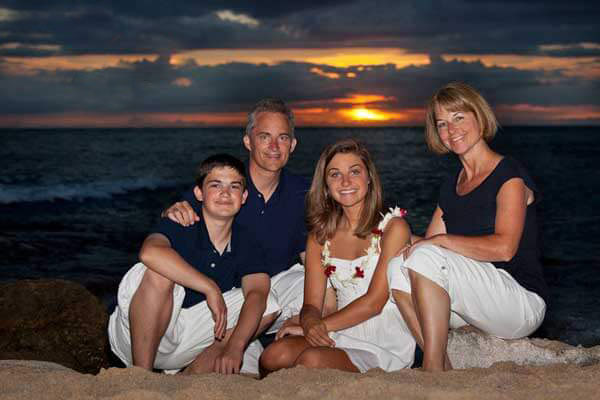 Beach Portrait of a Family wearing white and blue clothes for a photo session at Sunset at Secret Beach, Oahu, Hawaii